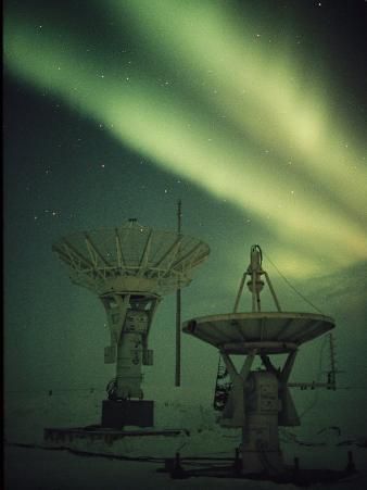 Antennas Point Skyward under the Glowing Aurora Borealis