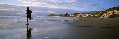 A Man Jogs Along Sands Beach Below Ellwood Bluffs, at Sunset