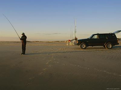 A Man Holds a Fishing Pole While Standing Near His Jeep Truck