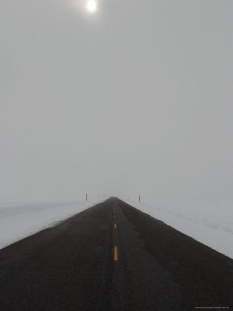 A Road Cleared of Snow Leads Toward the Horizon