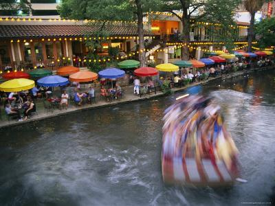 The Blur of a Passing Tourist Boat Along the Colorful Riverwalk