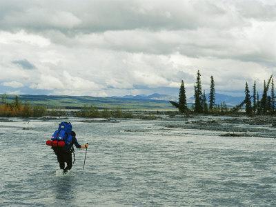 Man Carrying Backpack Crosses River in Denali National Park