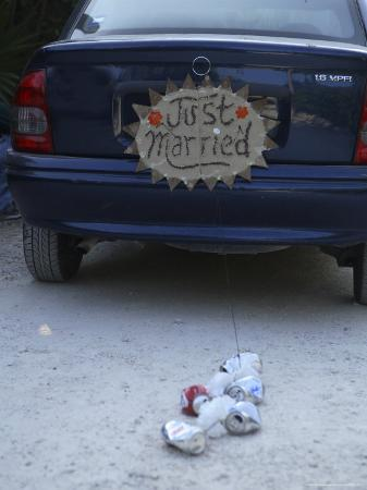 """A """"Just Married"""" Sign and Tin Cans are Atached to the Back of a Car"""