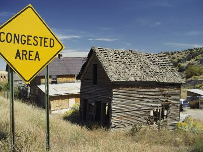 A Yellow Street Sign Reading Congested Area Next to a Run-Down Barn