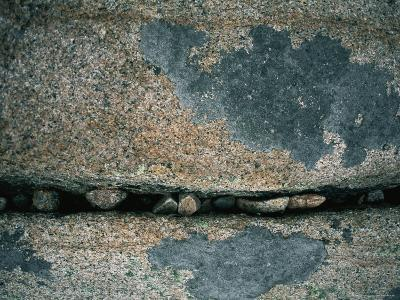 Stones Fill a Crack in a Large Rock