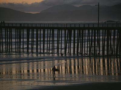 A Surfer Walks up the Beach Near a Pier at Twilight