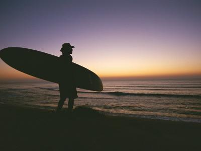 Silhouette of a Man with a Surfboard Looking out to Sea