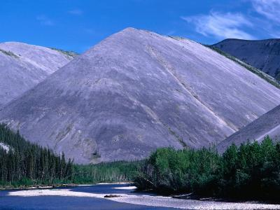 River Flanked by Spruce Trees and Bare Hills, Near Eagle Plains Ogilvie River, Yukon, Canada