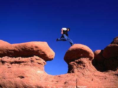 A Man Jumps onto a Hoo-Doo Formation in Goblin Valley, Goblin Valley State Park, Utah, USA