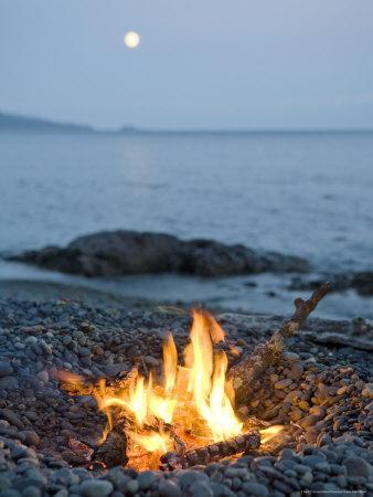 Campfire on a Beach with a Full Moon Visible