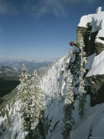 Man Rappels Down Red Mountain with a Snowboard on His Back