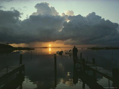 Small Fishing Boats Return to Dock as Clouds Gather at Sunset