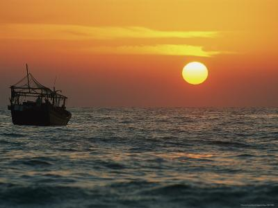 The Sun Rises Over a Fishing Boat on the Gulf of Oman