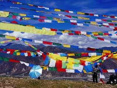 Pilgrim Stringing Up Prayer Flags with Mountains in Background