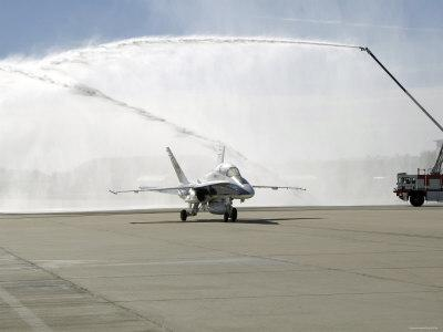 F-18 Aircraft Taxies Beneath the Spray from Fire Trucks