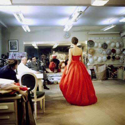 Fashion Designer Christian Dior Commenting on Red Gown for His New Collection Prior to Showing