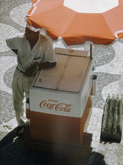 Coca Cola Vendor Leaning On Cart With Umbrella On Mosaic Sidewalk