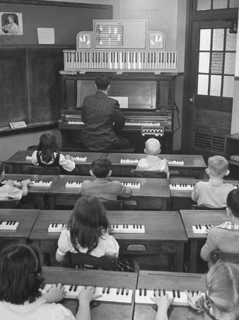 Elementary School Music Teacher Playing F-Major Chord on Piano, Keys Light up on Plastic Keyboard