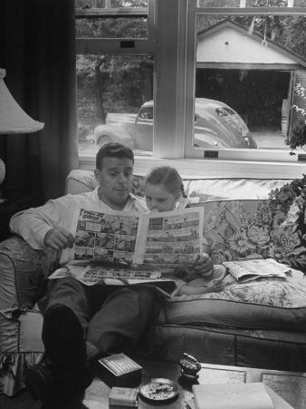 Father Sitting on Couch with Pigtailled Daughter Reading to Her the Sunday Comic Pages