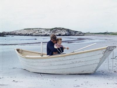 President John Kennedy and John Jr. Play in a Beached Rowboat at Newport, Rhode Island. 1962