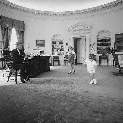 Caroline and John Jr. Dance in the Oval Office as President Kennedy Claps. 1962