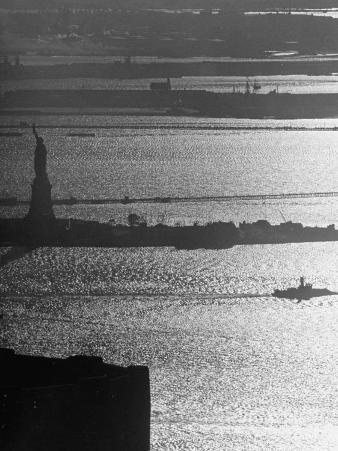 Moonlight on the Waters Surrounding Statue of Liberty as a Tug Boat Steams Past in New York Harbor