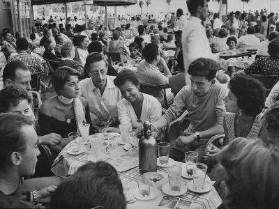 Crowded Outdoor Cafe in Rapallo, People Seated around Small Tables, Waiter Passing Through