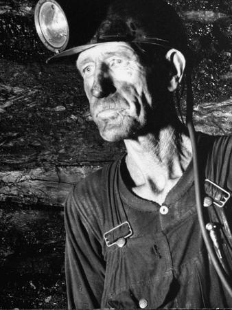Coal Miner with Head Gear on Working in Mine