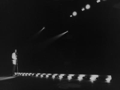 Singer Pat Boone Singing into Mike in Front of the Footlights on Stage in Auditorium