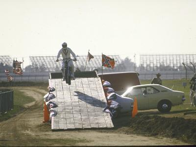 Daredevil Motorcyclist Evel Knievel Rising on Platform During Performance of Stunt