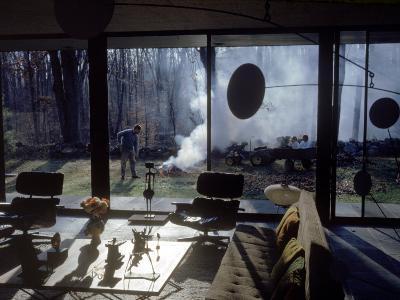 Architect Eliot Noyes Burning Leaves in Yard of Home He Designed Himself