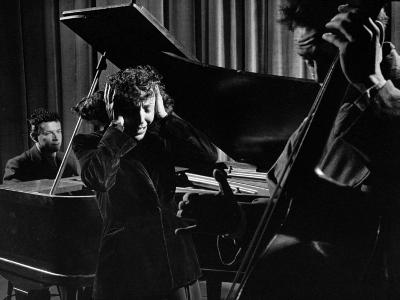 Singer Edith Piaf Holding Her Hands to Her Head While Performing with Pianist and Bass Player