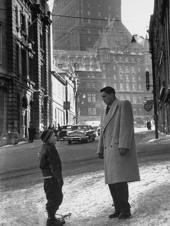 Ice Hockey Player Jean Beliveau, Standing in a Snow Covered Street Speaking to a Child
