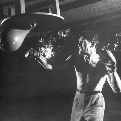 Actor Jack Palance in Boxing Trunks and Gloves, Hitting Punching Bag