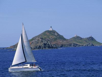 Sailing Boat with the Semaphore Lighthouse Behind, Iles Sanguinaires, Island of Corsica, France