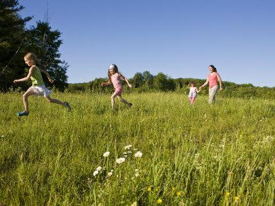 Hikeers walk in a field in Sabins Pasture, Montpelier, Vermont, USA