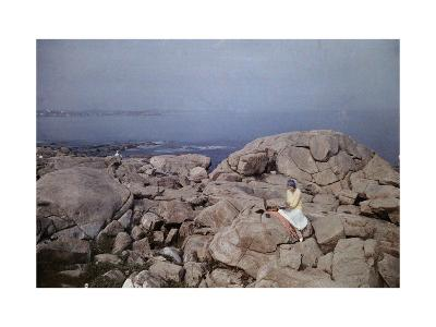Young Woman Sits Reading on the Rocks by the Water