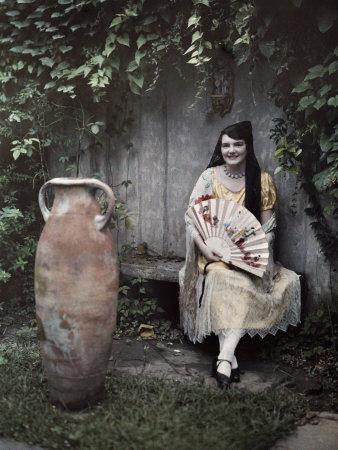 Young Lady Sits on a Bench by a Vase in a French Quarter Garden