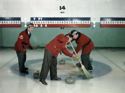 Red-Blazered Men Sweep Brooms on an Ice Rink in a Game of Curling