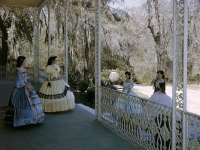 Women Stand on Antebellum Mansion's Porch Framed by Belgian Ironwork