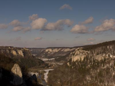 Winter Landscape with River, Snow, Leafless Trees, and Large Cliffs