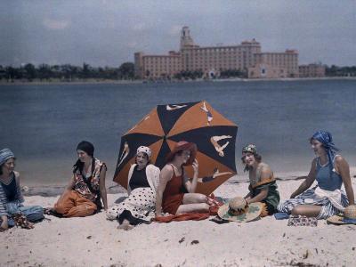 Six Women Sit on a St. Petersburg Beach with the Water Behind Them