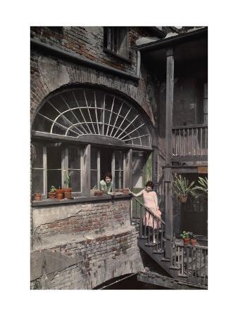 Two Women Stand by a Fan Window That Streams Sunlight into a Studio