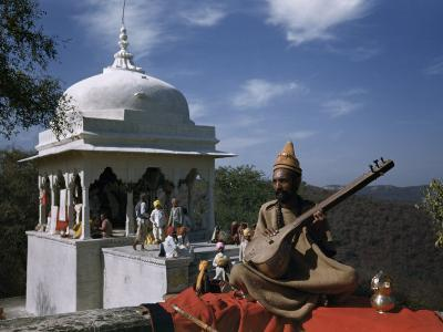 Holy Man Holding a Sitar Sits Cross-Legged Outside a Temple