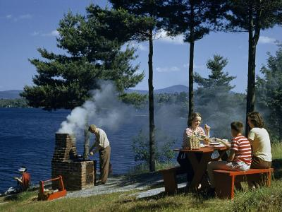 People Grill Food and Picnic on Hillside Overlooking a Lake