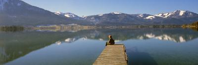 Woman Sitting on a Pier at Lakeside, Wolfgangsee, St. Wolfgang, Salzkammergut, Upper Austria