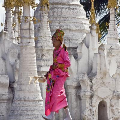 Myanmar, Burma, Lake Inle, A Young Novitiate Passes an Ornate Buddhist Shrine