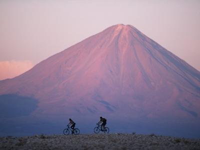 Mountain Biking in Atacama Desert Against a Backdrop of Perfect Cone of Volcan Licancabur 5916 M