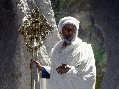 Old Ethiopian Orthodox Priest Holds a Large Brass Coptic Cross at Rock-Hewn Church of Adadi Maryam