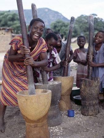 Cheerful Young Girls Pound Corn Outside Families' Homes Near Monkey Bay, South End of Lake Malawi